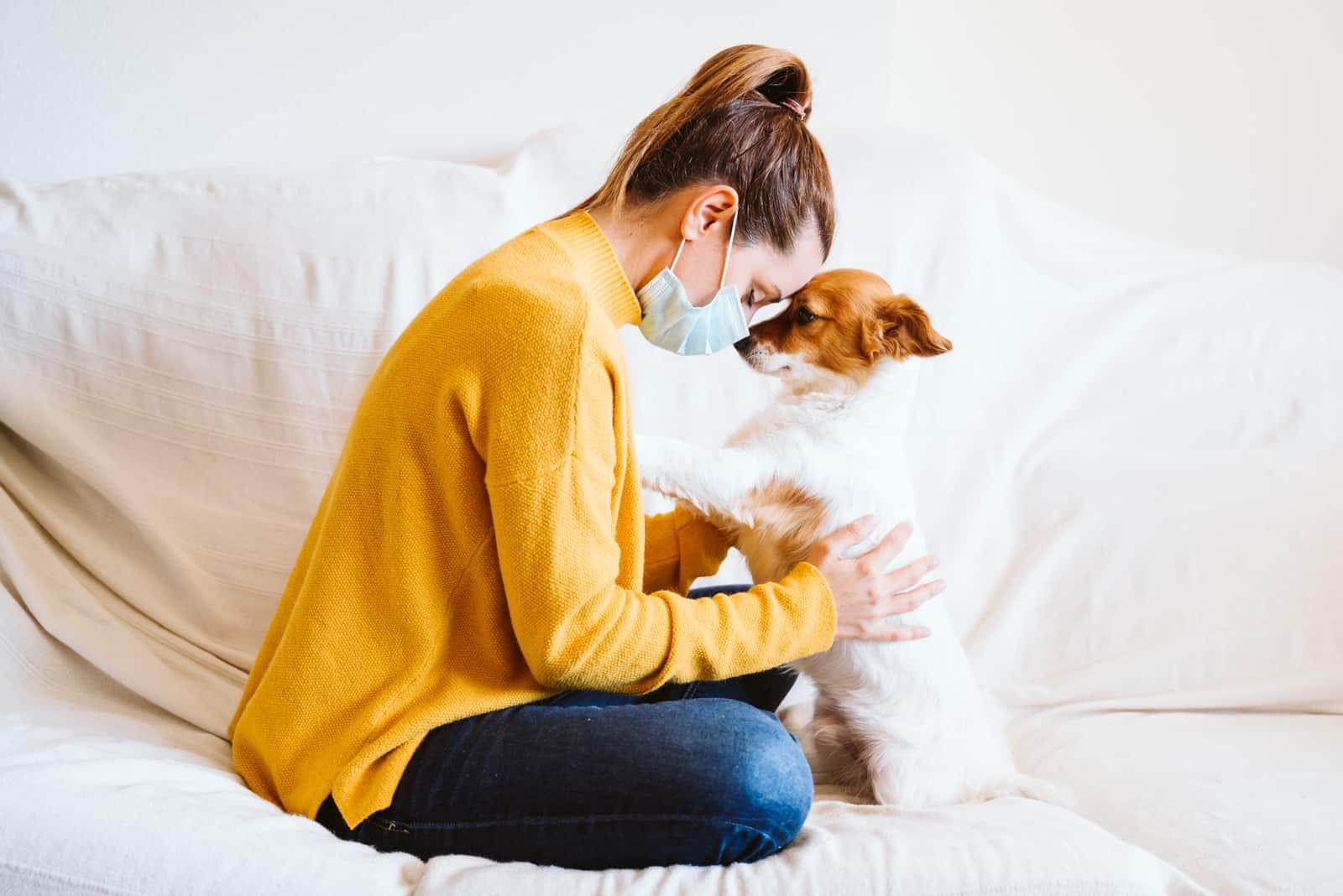 junge Frau, die ihren niedlichen kleinen Hund zu Hause umarmt