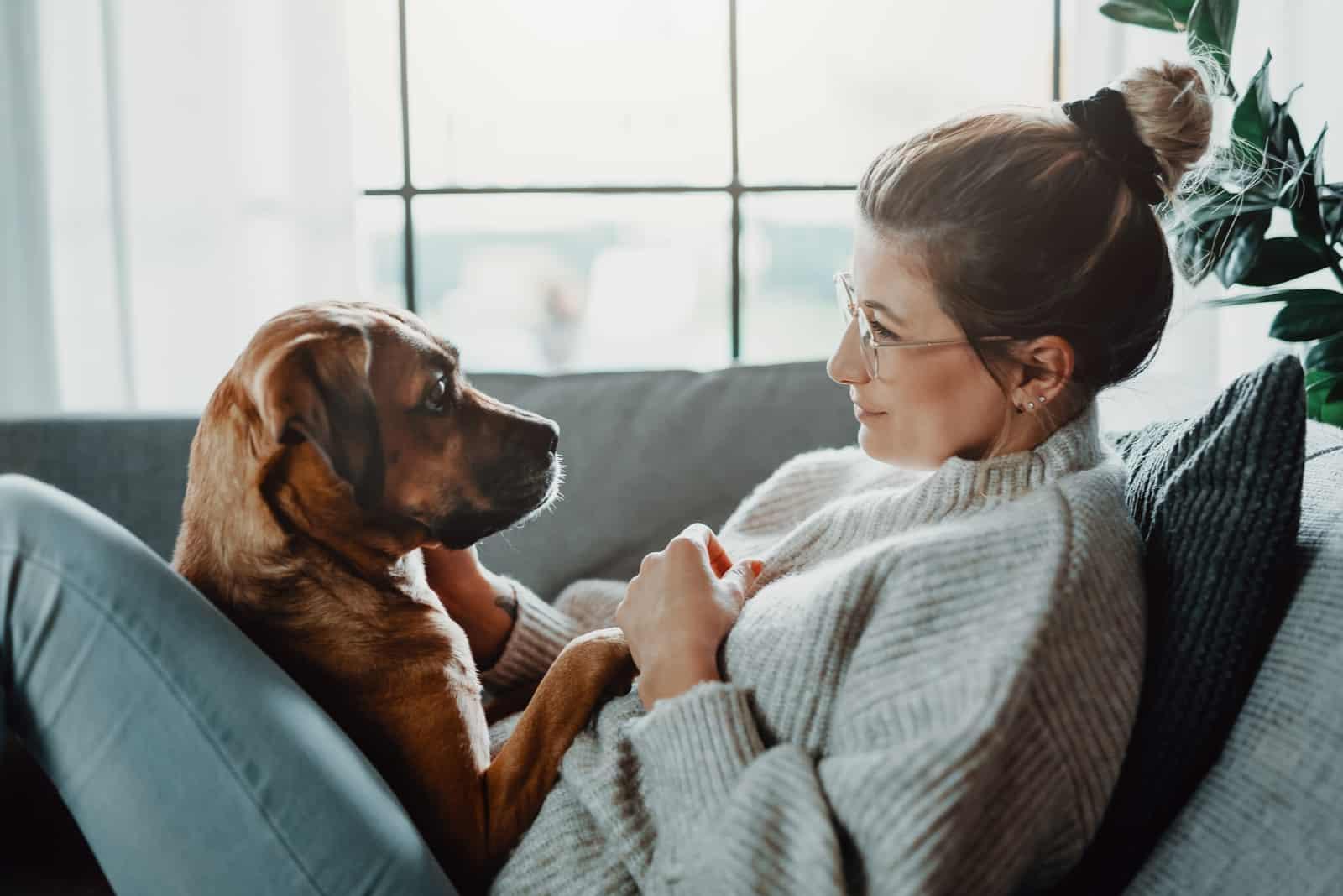 Frau kuschelt ihren Hund zu Hause