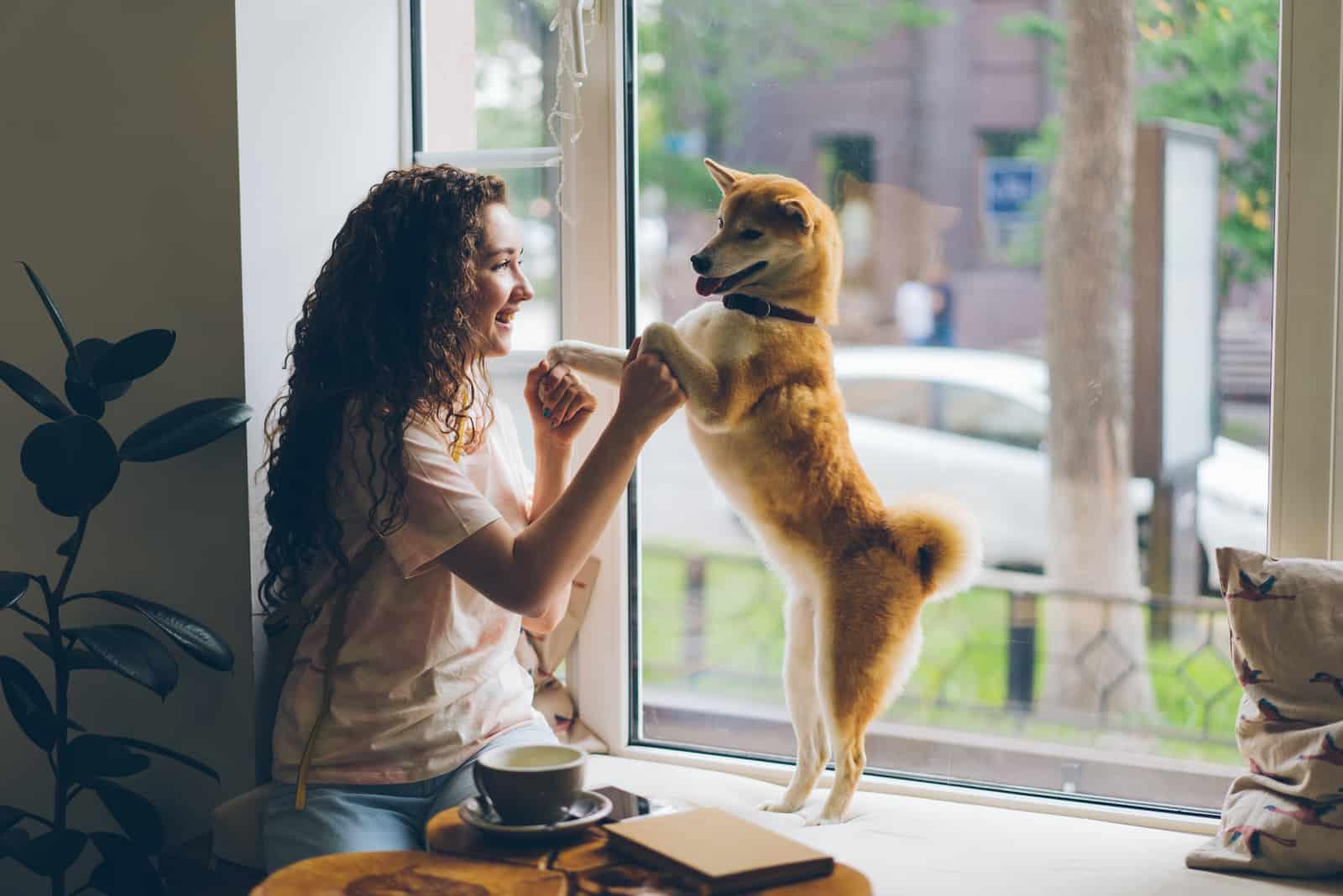 Glückliche junge Frau tanzt mit Haustierhund