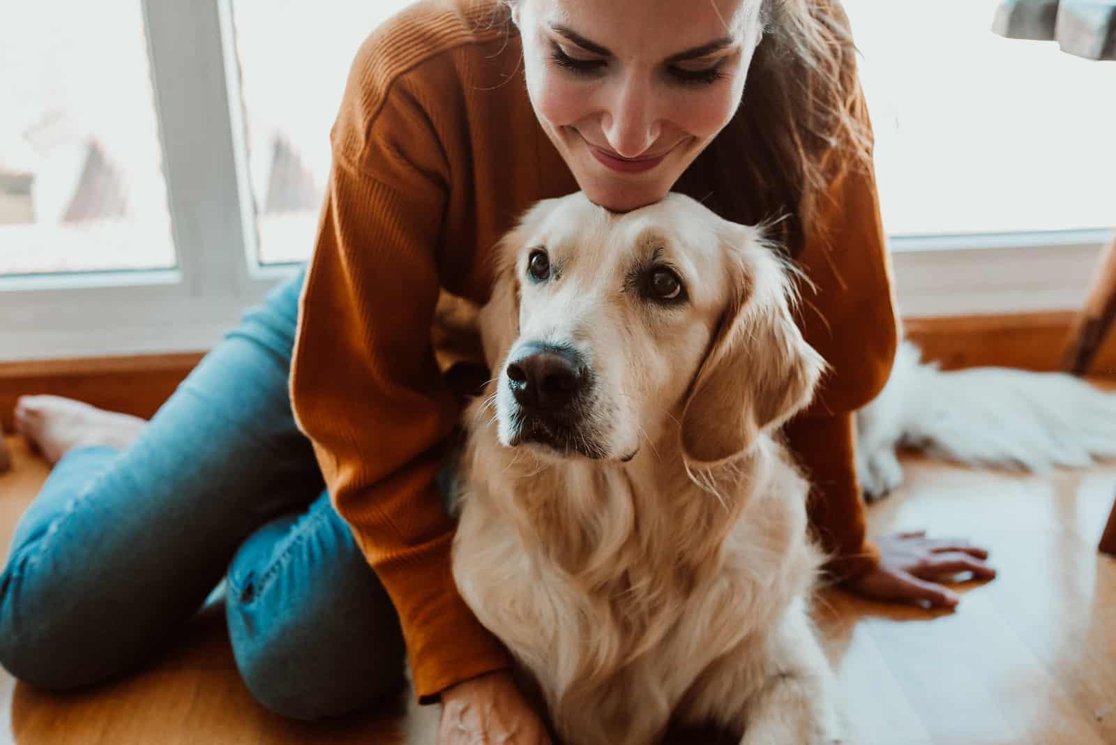 hübsche junge Frau, die ihren entzückenden goldenen retriver Hund kümmert und streichelt