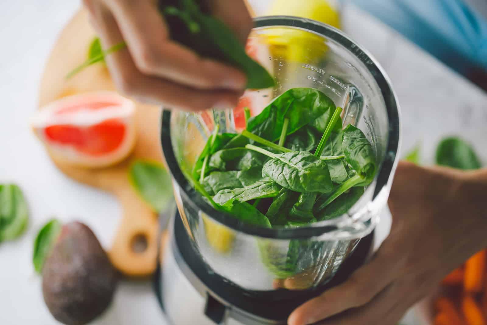 Ein Mann bereitet einen Spinat-Smoothie zu