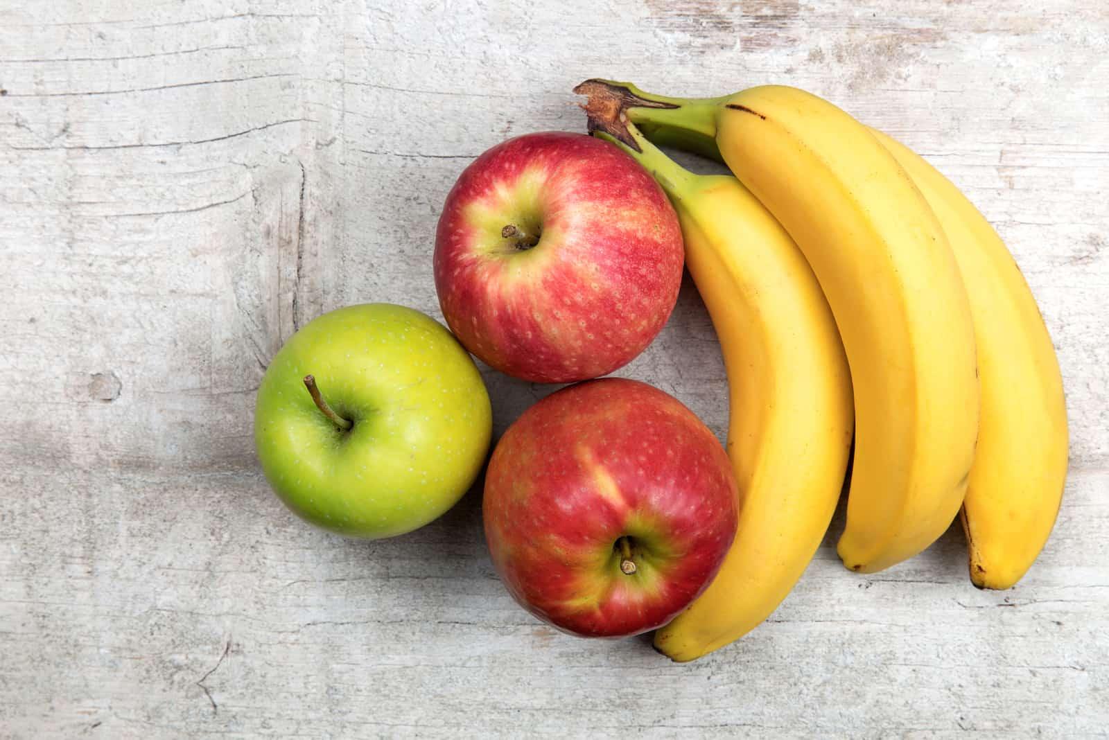 Äpfel und Bananen auf altem Holz