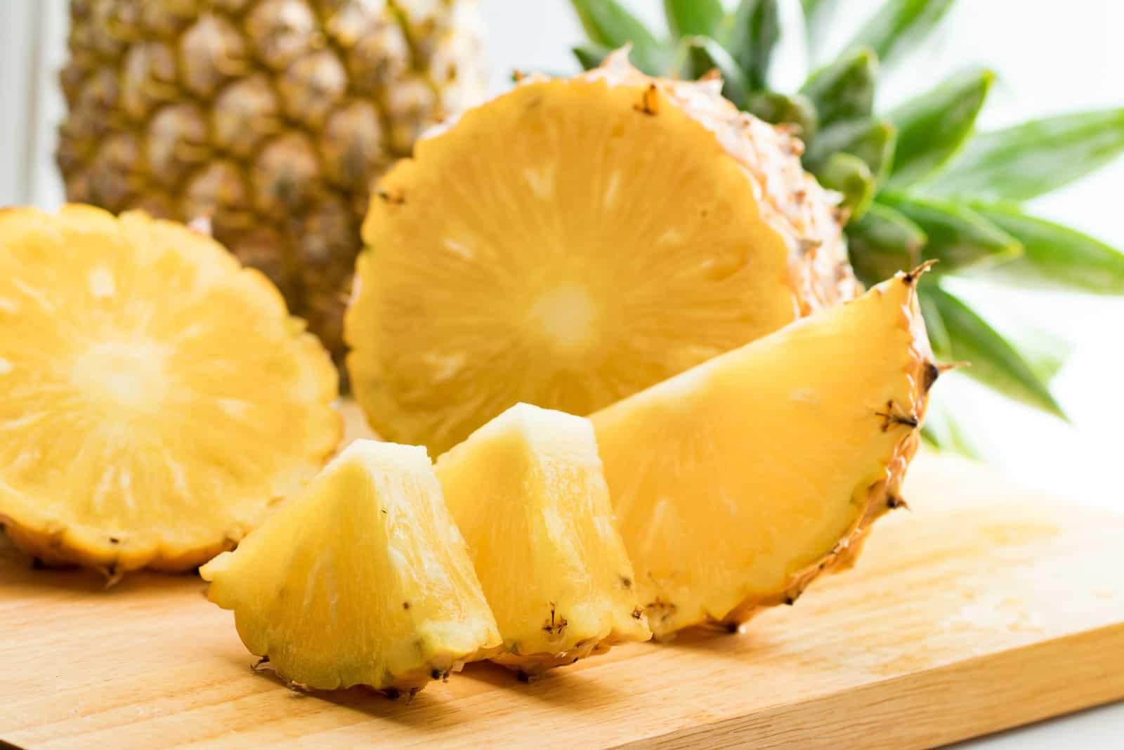 Ananasfrucht und Ananasscheibe auf Holztisch