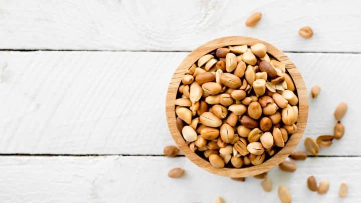 Geröstete Erdnüsse werden auf einen weißen Holzboden gelegt