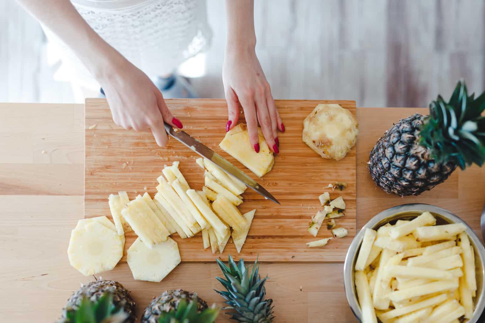 Frau geschnittene Ananas mit einem Messer auf dem Küchentisch