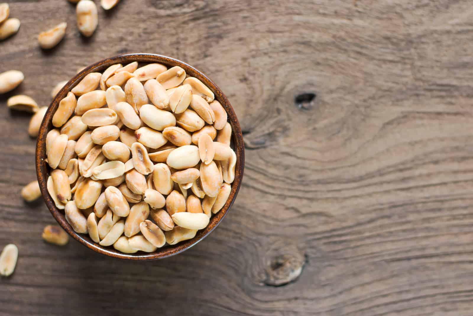 Geröstete Erdnüsse in eine Tasse geben