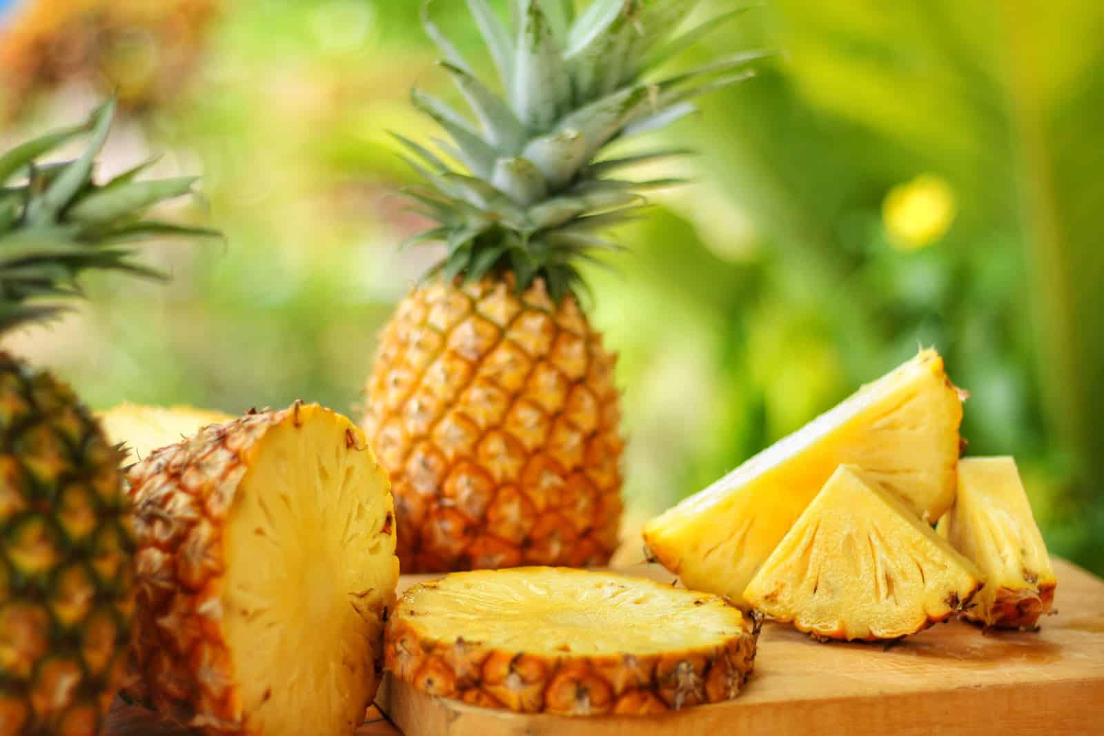 In Scheiben geschnitten und ganz Ananas auf Holztisch