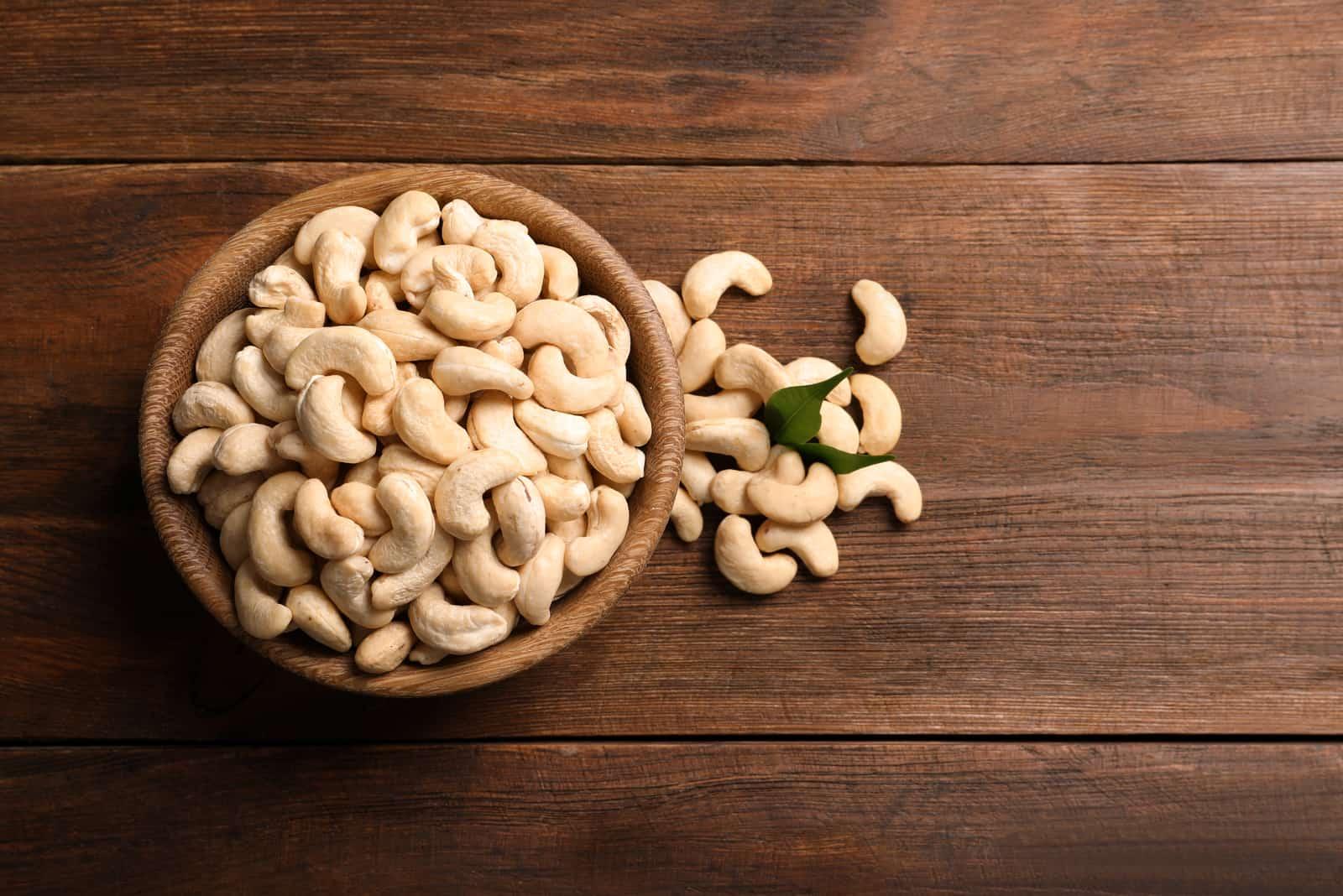 Leckere Cashewnüsse in der Schüssel auf Holztisch