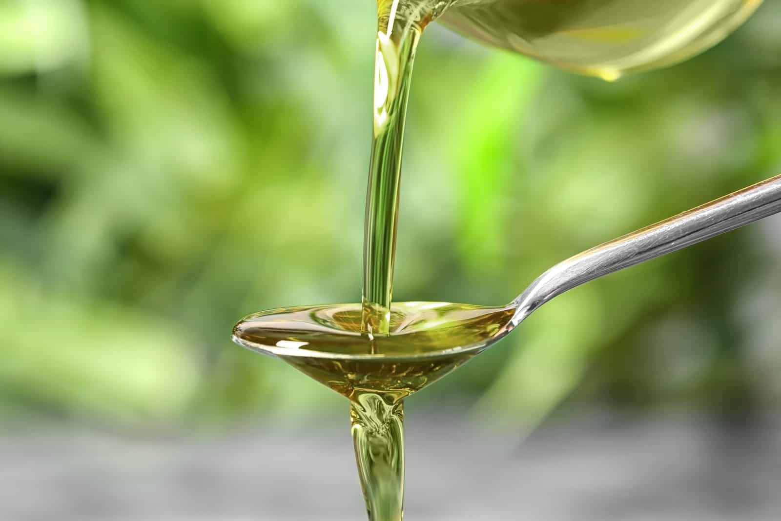 frisches Olivenöl wird mit einem Löffel gegossen