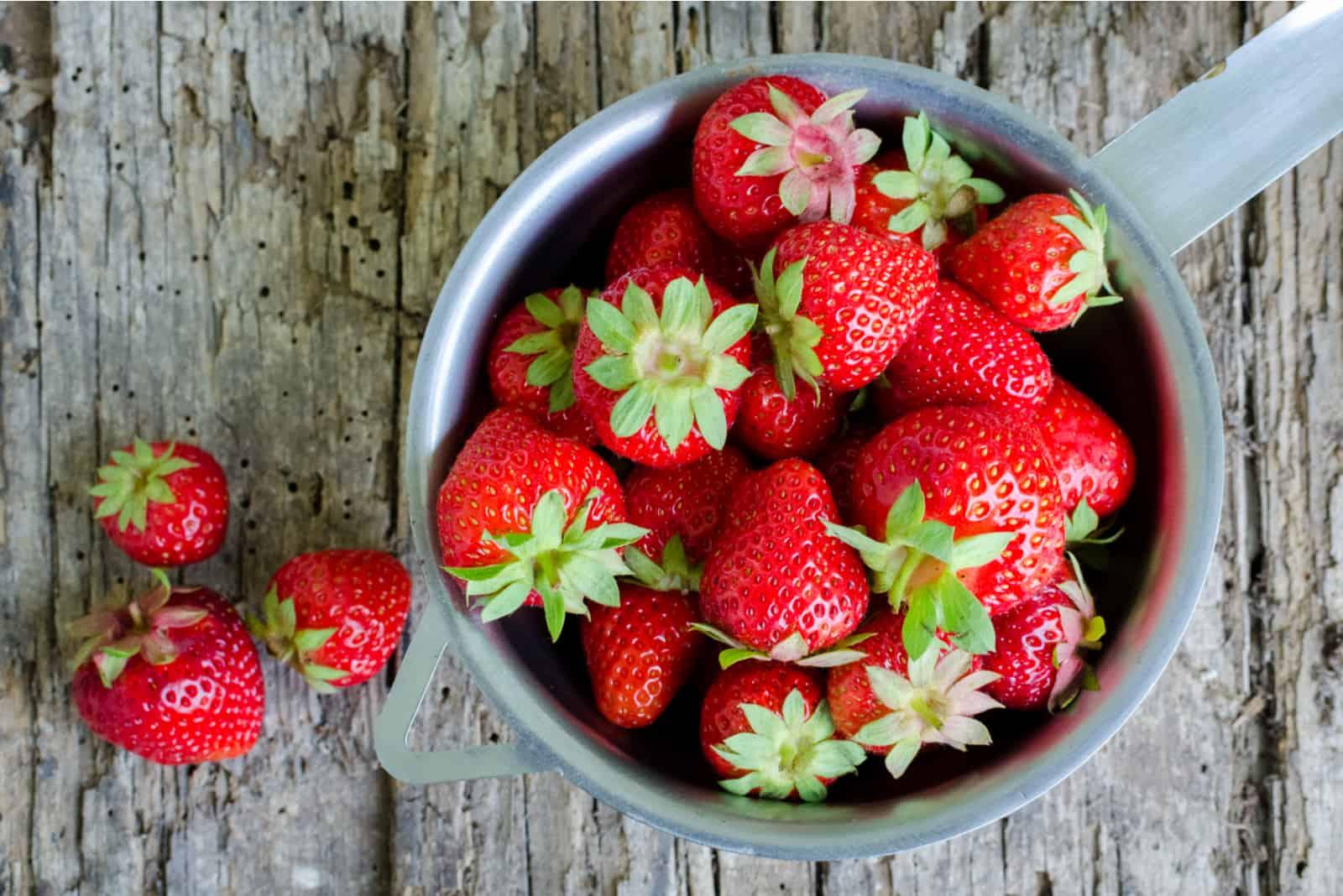 rote Erdbeeren auf einem alten hölzernen Beschaffenheitstisch