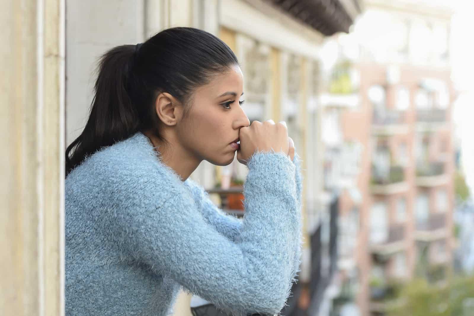 Eine traurige Brünette in einem blauen Pullover steht auf dem Balkon und denkt nach