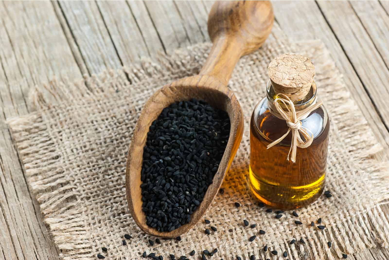 Ätherisches Öl der schwarzen Kreuzkümmel mit Holzlöffel