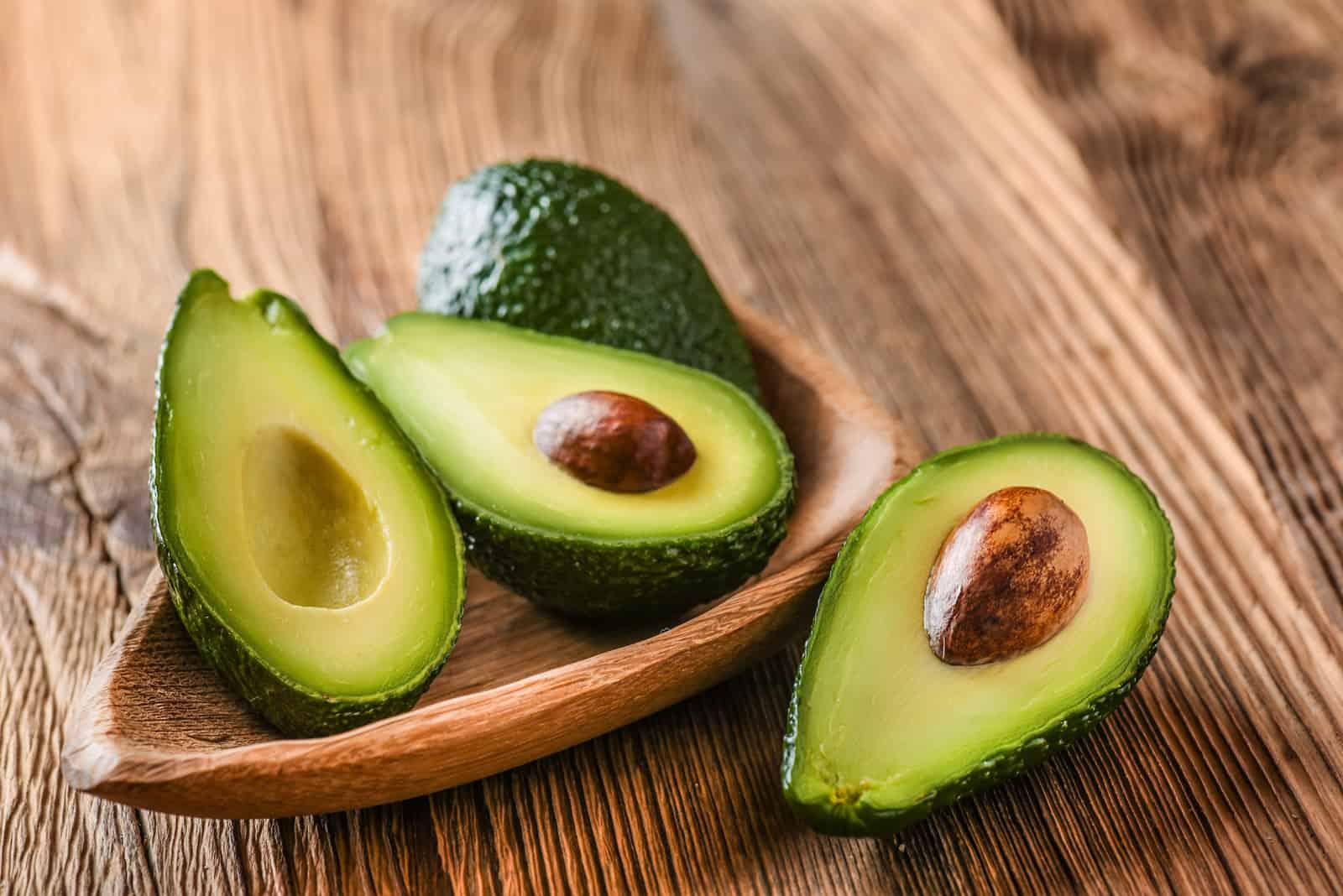 Avocado in einer Holzschale auf dem Tisch
