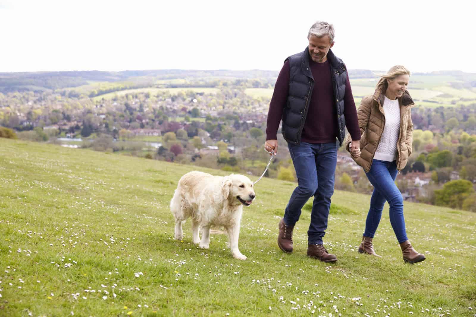 Ehepaar mit ihrem Hund auf einem Spaziergang