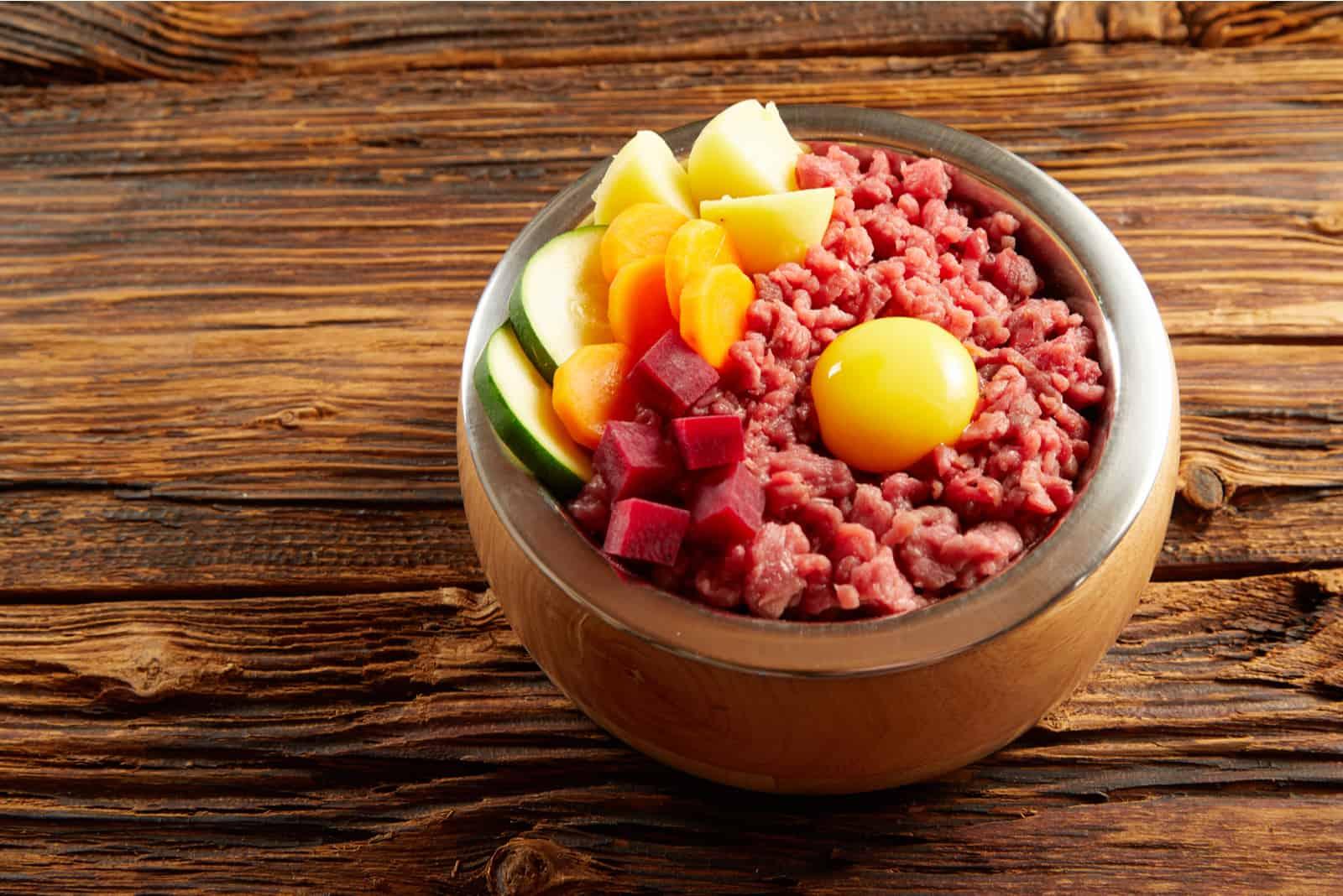 Leckeres Abendessen für einen Hund mit gehacktem und gehacktem rohem Fleisch, Eigelb und frischem Gemüse in einer Metallschale auf einem rustikalen Holzboden
