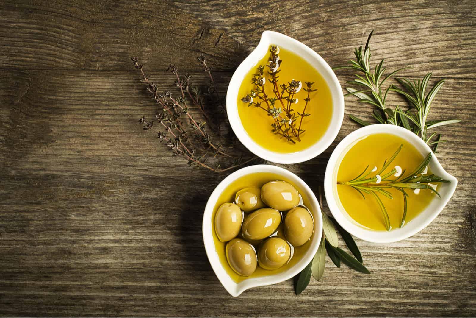 Olivenöl in Schalen auf einem Holztisch