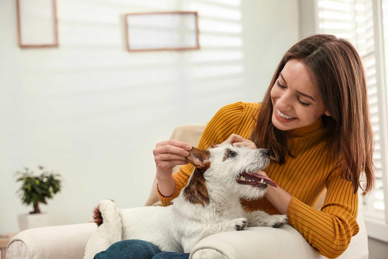 eine lächelnde Frau, die mit einem Hund spielt