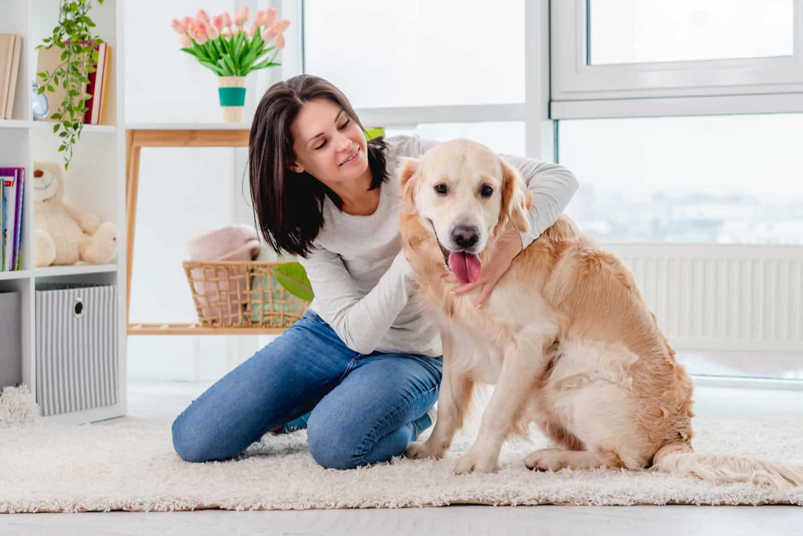 junges Mädchen streichelt Golden Retriever Hund