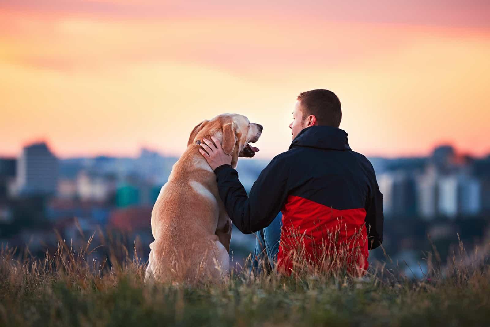 Junger Mann sitzt mit seinem Hund auf dem Hügel