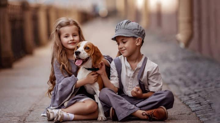 Süße Kinderjungen und -mädchen in Retro-Kostümen sitzen auf der Straße